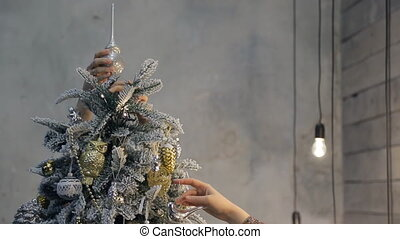 Two people decorating Christmas tree, top of mesh indoors
