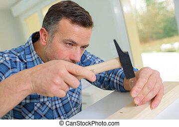 Man tapping nail into wood