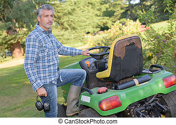 Man with leg raised onto ride on mower