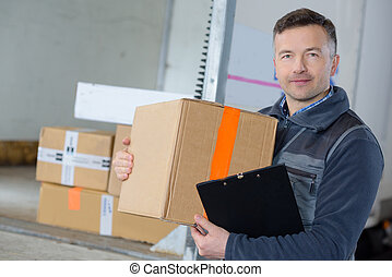 delivery man with parcel near cargo truck shipping service