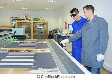 Man wearing protective glasses looking at printing machine