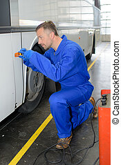 Mechanic screwing reflector on to bus