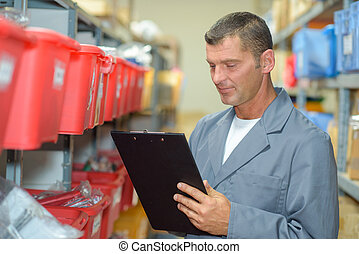 Man in warehouse with clipboard