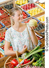 Lady holding melon and basket in greengrocers