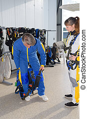 Man in jumpsuit stepping into harness