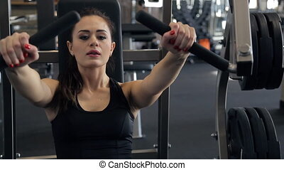 In the gym beautiful woman performs a bench press from the...
