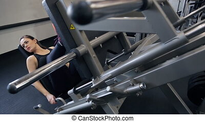 Young woman performing leg presses on a large metal...