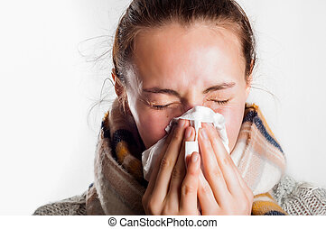Girl with cold sneezing in handkerchief wearing scarf and...