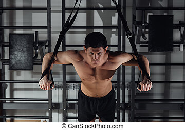 Attractive Man Does Crossfit Push Ups With Trx Fitness Straps In The Gym's Studio.