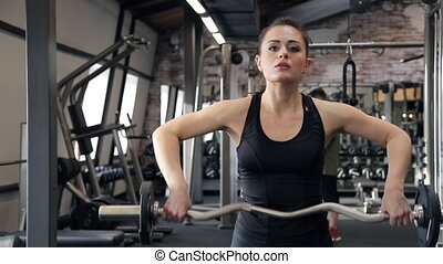 Woman in the gym lift the barbell with weight and lowers down.