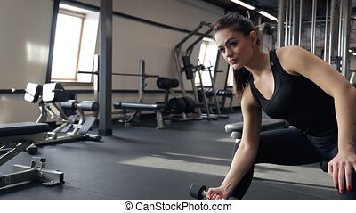 woman sitting, raises bar on hand, work out inside gym....