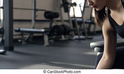 woman shakes biceps using dumbbells at gym indoors....