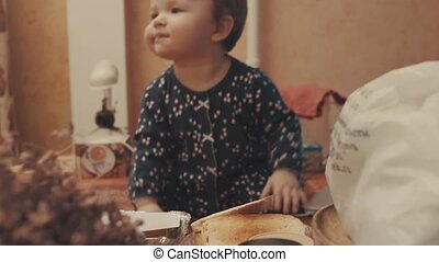 Little baby sitting on the table and eating biscuit. Middle...