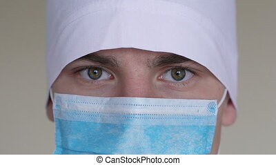 Close up of a male surgeon's face dressed in a surgical mask looking at camera