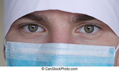 Close up of a male surgeon's face dressed in a surgical mask...