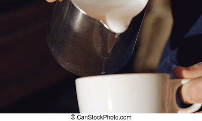 Male hands pouring milk into coffee, effect. Slowly