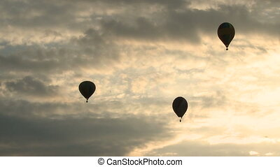 Silhouettes of air balloons in the evening sky.