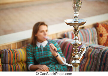 Beautiful young woman smokes a hookah in a cafe