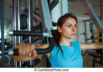 Woman works out on training apparatus in fitness center