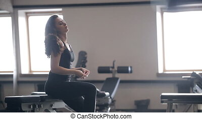 Woman resting after workout at trainers inside gym....