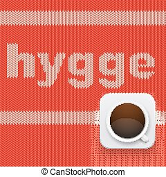 Word HYGGE on knitting texture with hot cup of coffee....