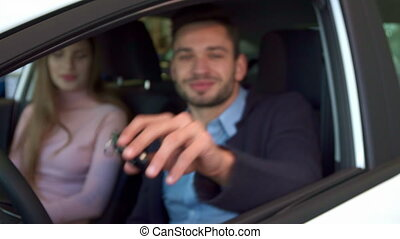 Man shows key through the car window - Close up of...