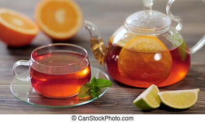 Glass teapot and cup of black tea with orange, lemon, lime...