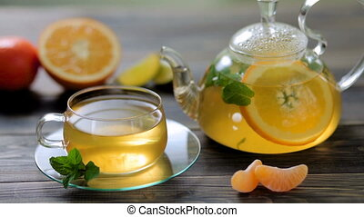 Glass teapot and Cup with green tea, orange, Mandarin, lime...