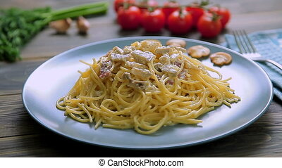 Spaghetti Carbonara with ham and mushrooms in blue plate on...