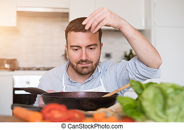 Man cooking at home and preparing food