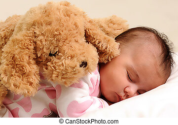 baby with white and pink sleepwear, sleeps with brown toy...