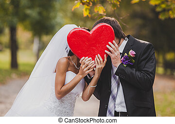 Happy wedding couple holds big red heart in hands. the groom and the bride hold    in hand.