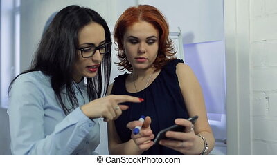 Two beautiful women discuss important information at office....