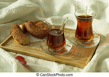 Morning turkish tea in traditional glass with bagel on the tray with two red hearts