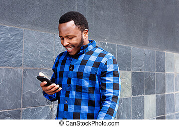 smiling black man looking at mobile phone