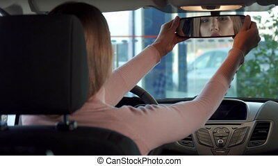 Girl looks into the rear-view mirror - Beautiful brown...