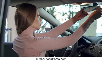 Girl adjusts rear-view mirror inside the car - Attractive...