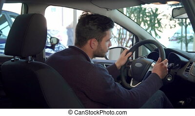 Man shows his thumb up inside the car - Handsome brunette...