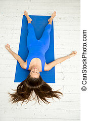 Top view of a woman in Corpse pose, white studio - Top view...