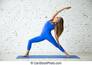 Young attractive woman in Reverse Warrior pose, white studio...