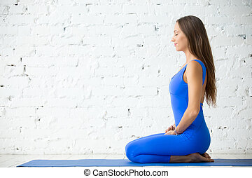 Young attractive woman in vajrasana pose, white studio...