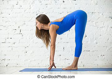 Young attractive woman in Ardha uttanasana pose, white...