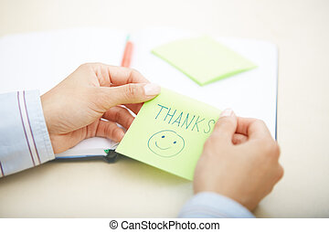 Thanks on adhesive note - Hands of woman holding sticky note...