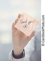 Thank you text on adhesive note - Woman holding sticky note...