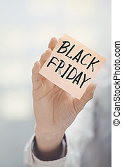 Woman holding adhesive note Black Friday text - Woman...