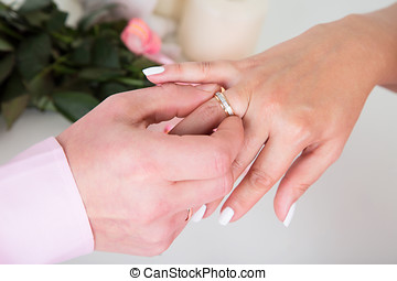 Hands with rings Groom putting golden ring on bride's finger...