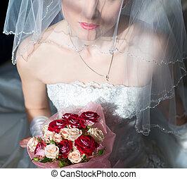 Wedding bouquet of roses in hands of bride.