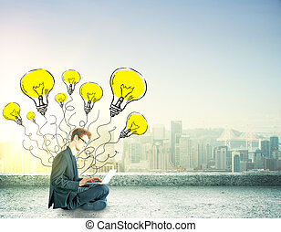 idea concept - businessman sitting with laptop with lighbulb...