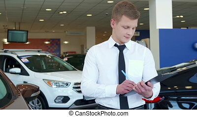 Sales manager shows car key at the dealership - Attractive...