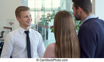 Salesman shakes hands with customer at the car dealership -...